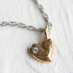 """A tiny diamond adds a touch of sparkle to this delicate, golden heart pendant with rustic, raw edges. Each necklace is designed and hand-crafted in Atlanta by mother-daughter team Avindy.- 18k gold vermeil, sterling silver, 1.5mm diamond, satin palladium chain, 14k gold fill clasp and extension- Lobster clasp closure- Pendant: 0.25""""W, 0.25""""L- Bib drop: 9.4""""- Handmade in the USA18.5""""L"""