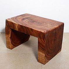 This elegant table showcases a solid carved piece dropping off the sides in an arc of a waterfall exposing the tree rings on both ends. This stylish table can be used as an end table or small coffee table that doubles as seating when needed.