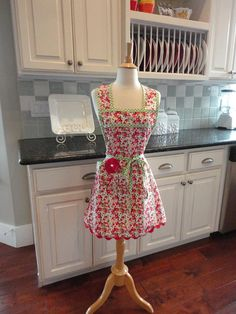 Our cute Simple Pleasures in red, navy and green floral - Annie Style Work Apron - Beautiful Quality - fabric with pretty red ric rac trim - This is a cute but functional apron. It loops over the neck and ties at the waist in the back. Waist tie can wrap around to tie in front as shown.