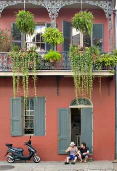 Two men sit on the porch of a French Quarter house with balcony above