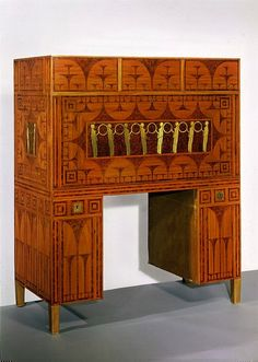 This desk with its 'disappearing chair' was based on various earlier models. These included early 19th century French desks in the Empire style, and German ones in the more solid and homely Biedermeier style. In these earlier models the chair was usually attached and released by mechanical means. In this example, however, Koloman Moser (1868-1918) decided that a large brass handle inserted into the back of the chair would perform the task equally well. He designed numerous chairs and…
