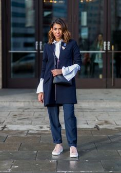 Storm Westphal combines a navy jacket and trousers with a bell-sleeved top and blush sneakers
