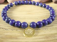 Lotus Bracelet This handmade Womens Bracelet design was inspired by Mala Beads and crystal healing wisdom. Made from high quality 6mm small beads, fits up to a 6 1/2 wrist.  Made with semi precious Lapis Lazuli beads. The deep midnight blue stones are flecked with golden Pyrite which perfectly compliments the Gold elements of the bracelet. This design features a Gold Plated accent bead with an antique finish and is finished with a genuine Thai Gold Vermeil lotus flower charm. This is a solid…