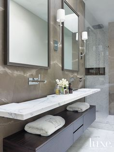 Floating cabinetry and book-matched suede marble walls define the master bath. Custom mirrors by Armand Lee are paired with sconces by Palme...