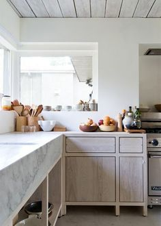 The white marble kitchen with stacks of wooden vessels and utensils in an artful display