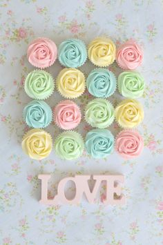 The word LOVE and cupcakes with pastel-colored frosting as a Valentine's Day display.