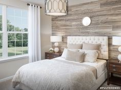 Soft earth tones set against bold wood patterns create depth for a cozy, rustic feel.   Pulte Homes