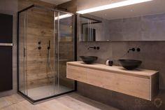 Moderne maatwerk badkamer met kerlite tegels met houtlook op de vloer. Wat een uniek effect geeft in combinatie met de grote grijze wandtegels en het grijze bad, de mat zwarte designradiator, het mat zwart toilet, de mat zwarte kranen op het bad, de douche en bij de wastafel en de mat zwarte Solid Surface (Corian) waskommen | #design_badkamers_breda #breda_design_badkamers