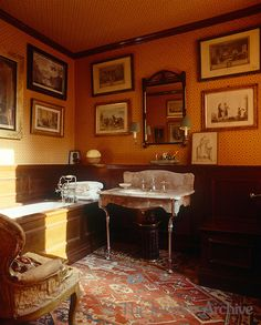 The walls and ceiling of this Victorian-style bathroom are lined in Geoffrey Bennison fabric