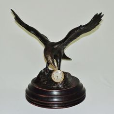 Escultura em bronze representando Águia em posição de ataque tendo ao bico relógio marca Silvana, me