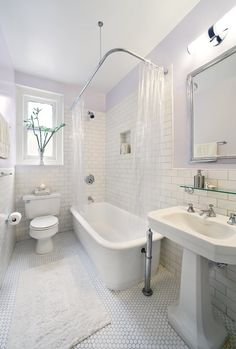 Traditional all-white bathroom with pillowed floor tiles.