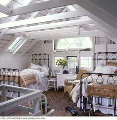 BEDROOMS Attic Exposed Beams Painted White Skylights Palladian Window Two Twin Black Iron Beds Gathered Bedskirts Striped Quilts White Crocheted Lace Bedding Natural Wicker Chiar White Dresser Sunflowers In Pitche Riding Boots And Attic Renovation, Attic Remodel, Black Iron Beds, Black Beds, Palladian Window, Barn Bedrooms, Attic Bedroom Designs, Attic Design, Exposed Beams