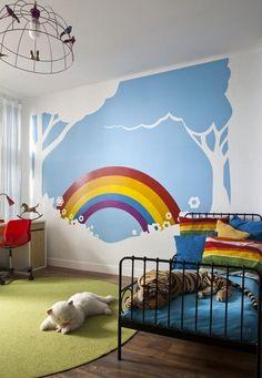 chambre enfant avec un lit en métal et déco murale arc en ciel