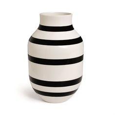 Den härliga Omaggio vasen kommer från det danska varumärket Kähler och är designad av Ditte Reckweg and Jelena Schou Nordentoft. Vasen är tillverkad i keramik av hög kvalitet och har ett handmålat randigt mönster som är typiskt för Omaggio-serien. Den tidlösa och enkla designen gör vasen enkel att placera i de flesta miljöer och kan enkelt matchas med andra produkter från Kähler för att skapa en modern och trendig känsla. Välj bland olika färger.