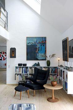 Bibliotekshjørnet er læsepladse med Wegners Bamsestol med fodhviler og Nana Ditzels lille trissebord. Malerierne er af Poul Winther og Erik Ejersen. Keramik fra Kähler og vase af Bindesbøll