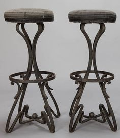 Pair Bar Height Stools with Fer Forge Base  --  Circa 1930s pair French wrought iron bar height stools with decorative scroll work bases, footrests, and round, upholstered seats. Sold and priced as a pair.  --   Item:  6913  --  Retail Price:   $1795