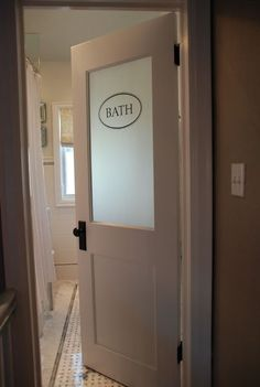 To help the room feel as open as possible, they installed a door with a frosted glass window in it, and then finished it with a vintage-style sign.