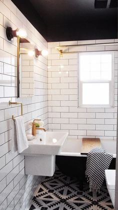 Elongated subway tiles in black and white bathroom with brass accents.