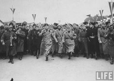 Benito Mussolini goose stepping ahead of his entourage, 1938