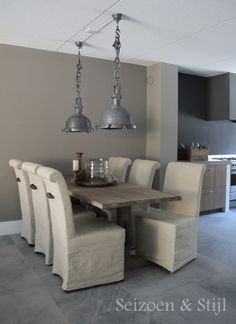 the stunning dining area in the kitchen of blogger Seizoen & Stijl - linen slipcovered chairs, rustic wooden table in a soft palette of grey, and taupe