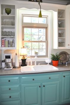 Turquoise bottom cabinets -- open shelving on either side of window--- and white upper cabinets