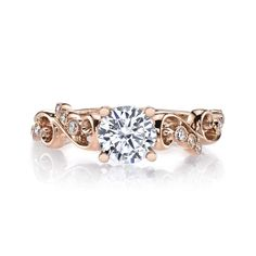 A Floral Motif Engagement Ring with Scrolling Metalwork and Diamond Accents Stones. Shown in Rose Gold with Approx. Three Quarter Round Brilliant Cut; Center excluded from Price. Side Stones: 0.08 Carat Weight Total.
