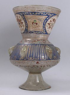 Mosque lamp Date: 14th century Geography: Egypt or Syria Culture: Islamic Medium: Glass, colorless with brownish tinge; free blown; enameled with red, blue, white, yellow, and green; gilded; six loops for suspension and foot attached. Dimensions: H. 11 1/16 in. (28.1 cm) Max. Dia. 7 5/16 (18.6 cm) Classification: Glass