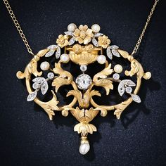 A thoroughly lovely and very feminine pendant necklace, circa 1900, exquisitely sculpted in richly textured 18 karat yellow gold. A gorgeous and graceful foliate design, crowned with a bouquet filled vase on top, twinkles with tiny rose-cut diamonds and a central antique cushion-cut diamond, all of which are set in platinum. A smattering of tiny natural pearls add shimmer to this extra sweet and lovely antique necklace with a hint of Art Nouveau style.