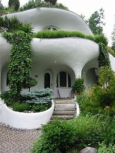 Cob home. I love the greenery spilling down from the roof! The very organic shape of the house fits in with the botanicals.