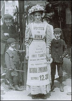 Women's Social & Political Union advertising for a great rally -- more comfortable than a sandwich board. Note the boys watching her -- street urchins often harassed suffragettes with the tacit approval of police.