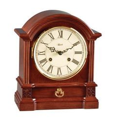 Hermle Hollins Barrister Style Table Clock 22915-N90130. h1Hermle Hollins Barrister Style Table Clock 22915-N90130_h1The Hermle Hollins Barrister Style Table Clock 22915-N90130 has fluted molding, starburst carvings and a brass handled drawer in addition to an ivory colored dia.. . See More Table Clocks at http://www.ourgreatshop.com/Table-Clocks-C1125.aspx