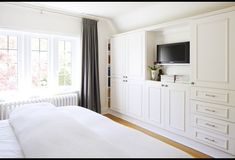 Bedroom: Wall of built-in cabinets for storage with space for tv, rather than a normal closet. Cynthias Designer Inspired Romantic Home
