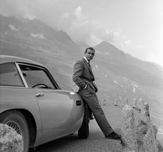 Sean Connery's Bond leans against the famous 1964 Aston Martin DB5 from Goldfinger, up in the Alps.
