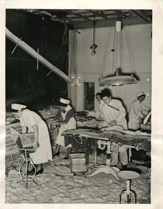 1940- Cleaning up the debris in the operating room of the famous Robert Koch Hospital in Berlin after in was struck by a bomb during R.A.F. night raid.