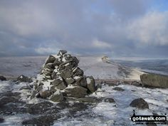 Swarth Fell summit cairn in the snow with Wild Boar Fell in the background