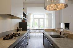 Moderne zwarte keuken met betonnen aanrechtblad. Een betonnen aanrechtblad geeft je keuken een stoere en robuuste look. Helaas moet je wel tegen vlekken kunnen want beton is erg vlekgevoelig. Bij deze keuken is er bovendien voor gekozen om losse gaspitten in het aanrechtblad te plaatsen in plaats van een gaskookplaat.