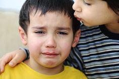 niño llora hermano consuela