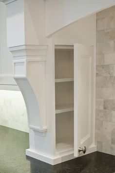 This spice cabinet is conveniently located for easy access within the columns that frame the range hood.