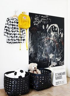 I love these black baskets! What a gorgeous way to store kids outdoor toys in an entry way (though this whole look would work just as well in a child's bedroom or play room). I love the hooks to hang jackets and the chalk board could keep one child entertained while you get another organised.  Perfect!