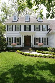 Center hall colonial house with black shutters and front lawn.