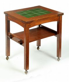 """GUSTAV STICKLEY: Table with grueby tiles; early 20th century. Oak table with mortise and pegged top arched apron and lower shelf with key and tenon construction, twelve green Grueby tiles decorate the top, Excellent condition, signed, 28.25""""h."""