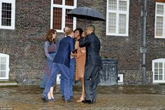 Mrs Obama was greeted with a kiss on the cheek by Prince Harry when the President and Firs...
