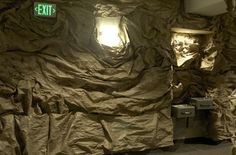 Crumble up brown paper, use brown tape and paste on walls.