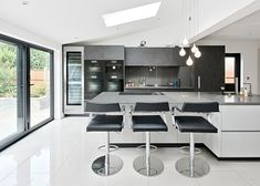 Professional chef Monica Galetti's kitchen features grey banks of cupboards with a large central grey island, giving it an industrial vibe. Appliances include a Miele Oven, SousChef Food Warming Drawer, Panoramic Induction Hob, Barbecue Grill, Gas Hob, MasterCool Fridge Freezer, Combination Steam Oven, Sous Vide Vacuum Sealing Drawer, Coffee Machine, MasterCool Wine Conditioner, Dishwasher, Cooker Hood and Microwave; all helping Monica to create restaurant results at home
