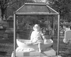 The children under glass are life size white marble statues of the children buried there. (It is said that some of the statues of children in the cemeteries were made from their death masks. A common practice in the Victorian period.) A boy in a boat with his toys and a girl standing with flowers in her hand. They were their mother's only children and their mothers are now buried next to them.