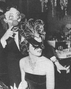 February 8, 1950: Oleg Cassini sneaks up behind wife Gene Tierney at a masquerade ball.