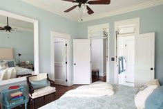 Operable transoms over the doors are fitted with vintage hardware and funnel light and air into this master bedroom
