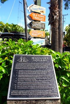 Directional arrows pointing the way to Key West attractions at Mallory Square