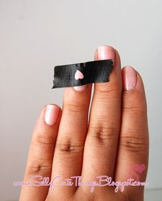 Use hole puncher and masking tape to make shapes on nail polish. Cute idea.