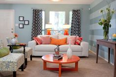 Bright and Beautiful  LIVING ROOM, AFTER: The drab living room became a major selling point as vibrant orange accents and blue-gray walls make the space brighter and more welcoming. Mixed patterns in the curtains, walls and chairs work seamlessly together to add personality and texture.PROPERTY BROTHERS